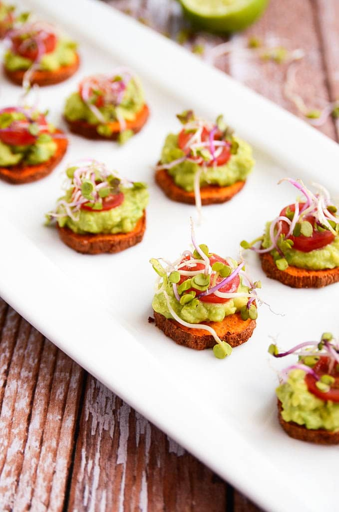 These vegan sweet potato + avocado bites make the perfect crowd-pleasing appetizer! Sweet potato slices are tossed in olive oil, cumin, and paprika and roasted to tender perfection. A creamy mixture of avocado and lime juice is dolloped on top, and the little stacks are then garnished with a slice of tomato and radish sprouts. These bites are vibrant, zesty, and addictive!